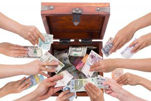 many hands putting money into an open chest
