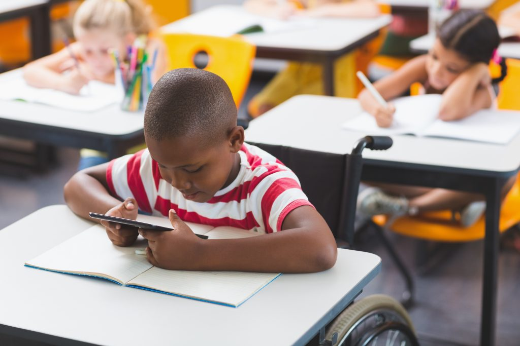 boy in wheelchair using tablet