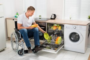 Man in wheelchair loading dishwasher in accessible kitchen
