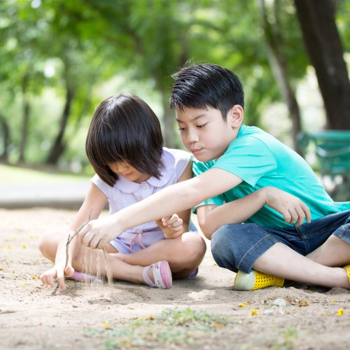 children playing in the sand at a park
