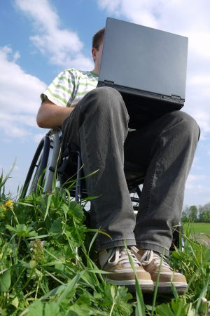 Man in a wheelchair using laptop computer outdoors