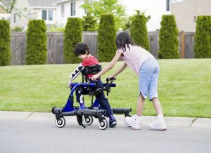 Big sister helping younger brother to walk in his walker outside