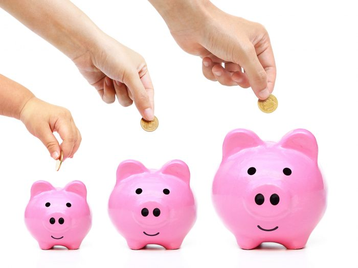 family saving money in piggy banks