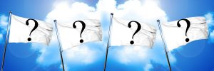 white flags with question marks agains a cloudy sky