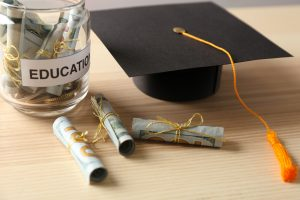 Graduation hat and glass jar with money for education on wooden table