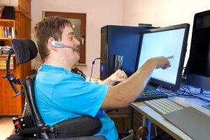 Man sitting in a multifunctional wheelchair using a computer with a wireless headset, reaching out to touch the touch screen.